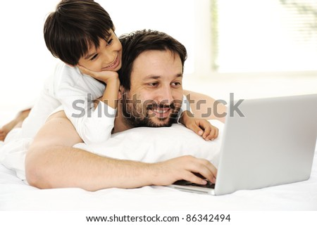 Father and son in bed, using laptop together, happy time - stock photo