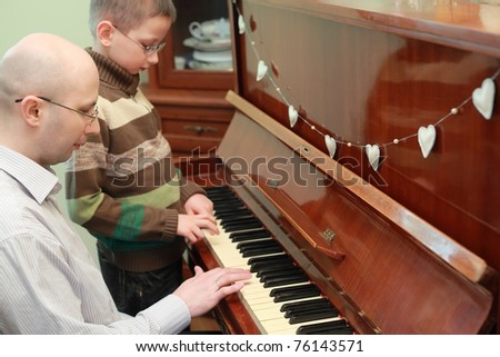 Father and son in glasses playing piano, concentrated faces - stock photo