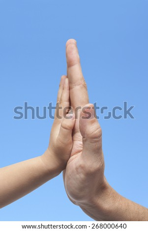 Father and son in high five gesture on a blue sky background - stock photo