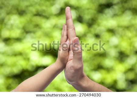 Father and son in high five gesture on a blurred natural green background - stock photo