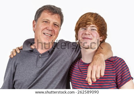 father and son in puberty arm in arm - stock photo