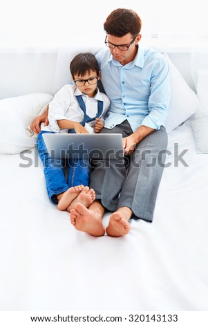 Father and son in stylish optical eyeglasses browsing internet. Dad is lying on the bed , helping son to do his homework.