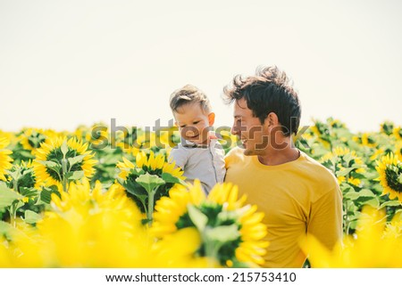 father and son in sunflower field - stock photo