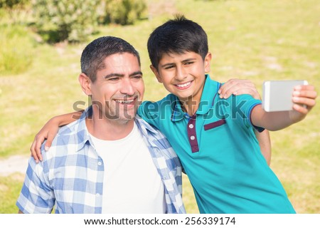Father and son in the countryside taking selfie on a sunny day - stock photo