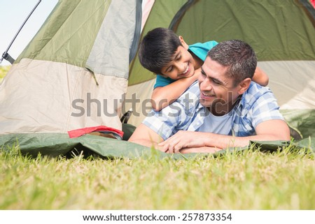 Father and son in their tent in the countryside on a sunny day - stock photo