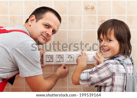 Father and son installing electrical wall fixtures together - working around the house - stock photo