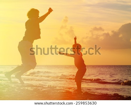 father and son jumping at sunset beach - stock photo