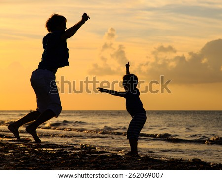 father and son jumping at sunset beach