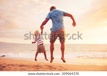 Father and son jumping for joy on the beach at sunset - stock photo
