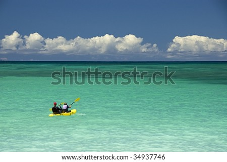 Father and son kayaking  on clear ocean water.