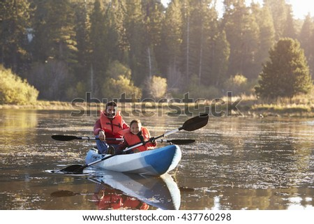 Father and son kayaking on rural lake, front view - stock photo
