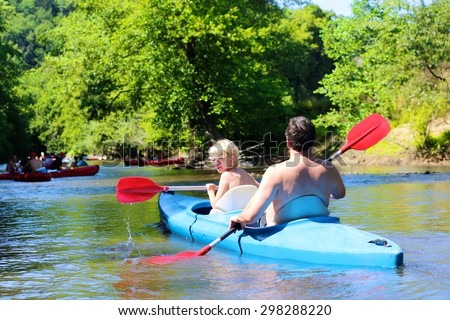 Father and son kayaking on the river. Active happy family, a man with teenage school boy, having fun together enjoying adventurous experience on a sunny day during summer vacation. - stock photo