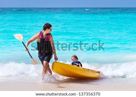 Father and son kayaking together on a tropical beach - stock photo
