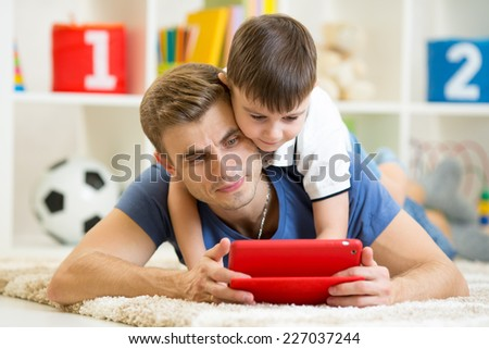father and son kid playing with tablet computer indoors - stock photo