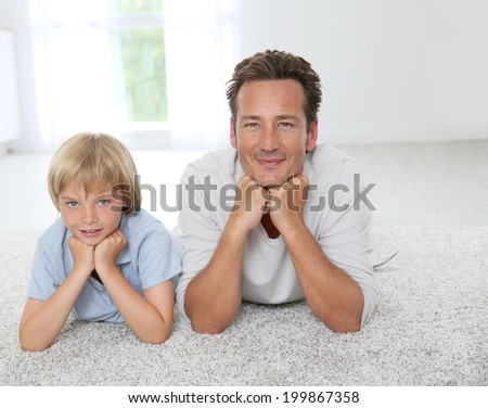 Father and son laying on carpet at home - stock photo