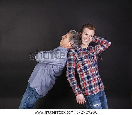 father and son lean together back to back isolated on black