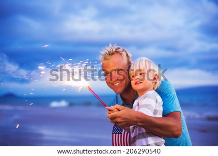 Father and son lighting sparklers on the beach at sunset - stock photo