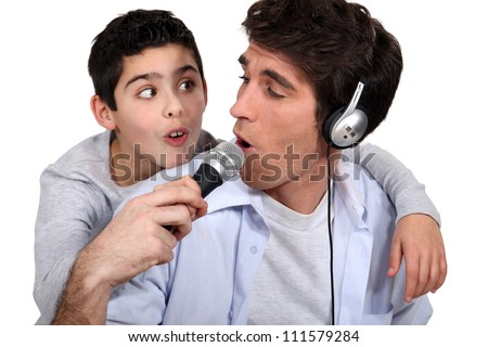 father and son listening music and singing - stock photo