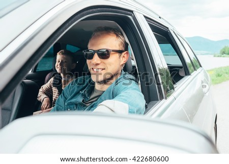 Father and son look out from car window - stock photo