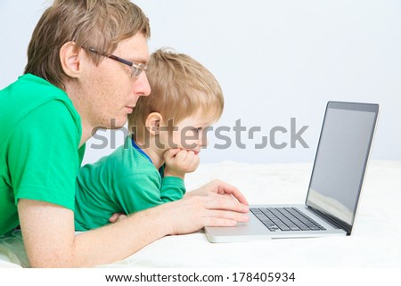 father and son looking at laptop at home - stock photo