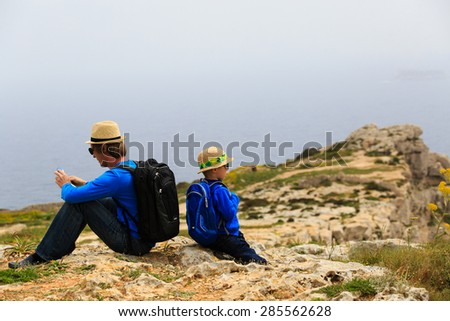 father and son looking at map while travel in mountains