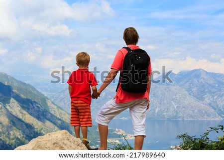 father and son looking at mountains on summer vacation - stock photo