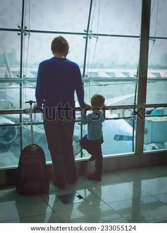 father and son looking at planes while waiting in the airport - stock photo
