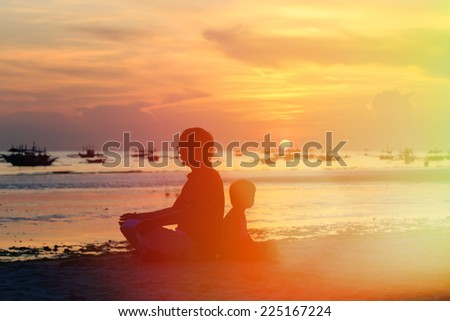 father and son looking at sunset on tropical beach