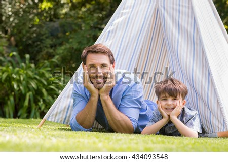 Father and son lying with their hands on cheek. Young boy and his dad smiling and looking at camera. Portrait of happy family playing with tent in the garden. - stock photo