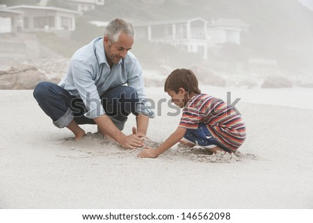 Father and son making sand castle together on beach - stock photo