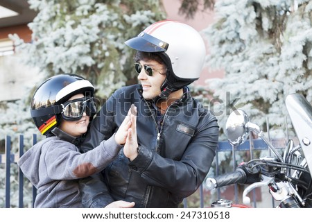 father and son motorcyclists high five