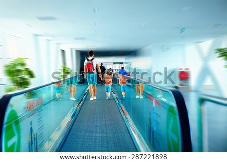 father and son moving on escalator after arrival in international airport - stock photo