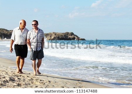 father and son on a beach - stock photo