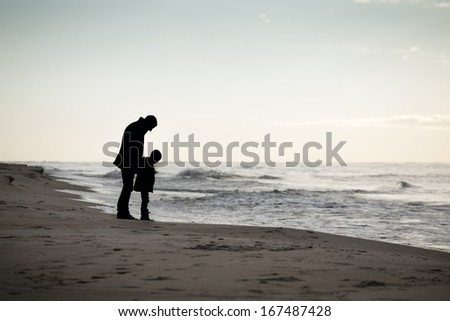 Father and son on a beach. Autumn walk. - stock photo