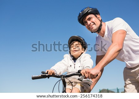 Father and son on a bike ride on a sunny day - stock photo