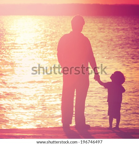 Father and son  on a dock at sunset, boy looking up at his father.