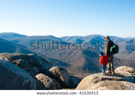 Father and son on a mountain top opened up admiring the view