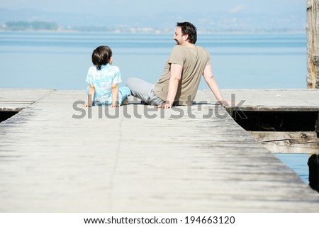 Father and son on a sea dock