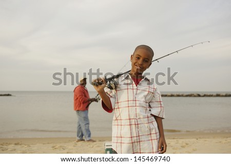 Father and son on beach with fishing pole - stock photo