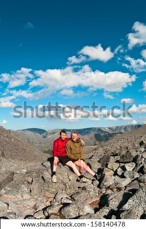 Father and son on peak of mountain. Two people family - stock photo