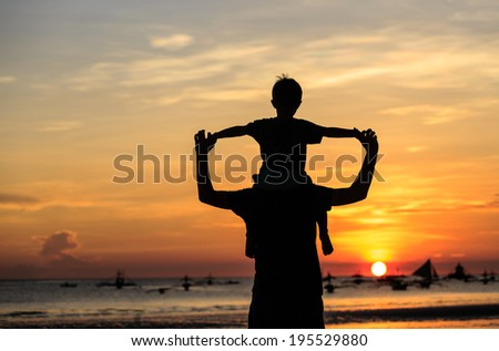 father and son on sunset beach - stock photo