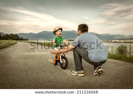 Father and son on the bicycle outdoor - stock photo