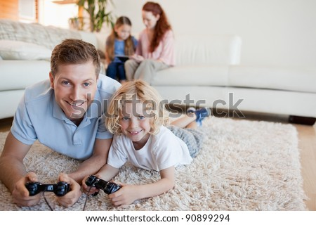 Father and son on the floor playing video games together - stock photo