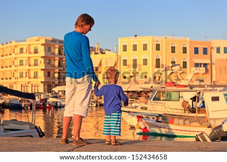 father and son on the quay in Crete, Greece - stock photo