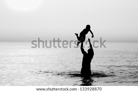 father and son on the sea at sunset - stock photo