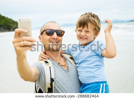 Father and son on the sea. Take foto on smarphone - stock photo