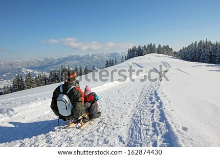 father and son on the sleigh, in the bavarian alps - stock photo