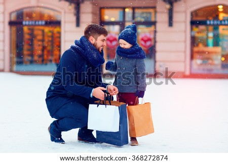 father and son on winter shopping in city, holiday season, buying presents