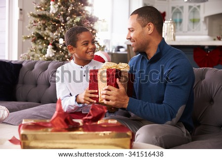 Father And Son Opening Christmas Presents At Home Together - stock photo
