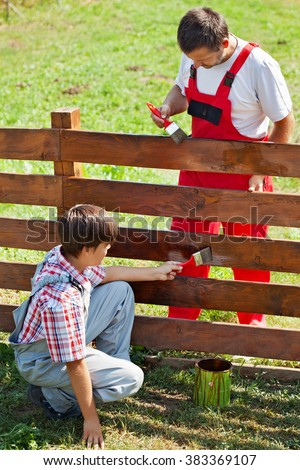 Father and son painting a garden fence on a sunny summer day